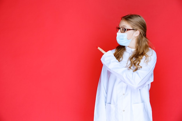 左向きのフェイスマスクの医者。