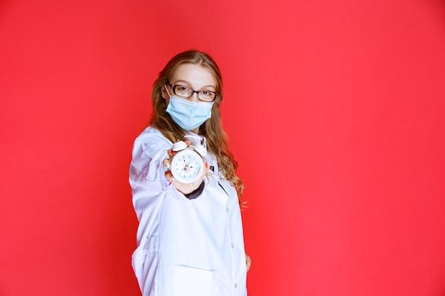 薬を服用する時間を意味する時計を示すフェイスマスクの医師。
