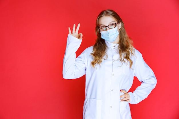 大丈夫な手のサインを示すフェイスマスクの医師。