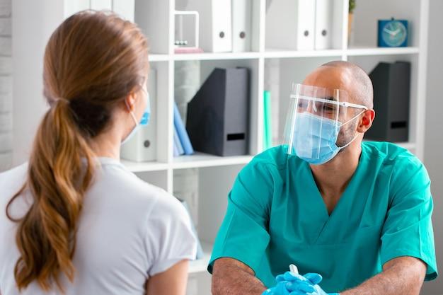 クリニックで女性患者と話しているフェイスマスクの医師のクローズアップ