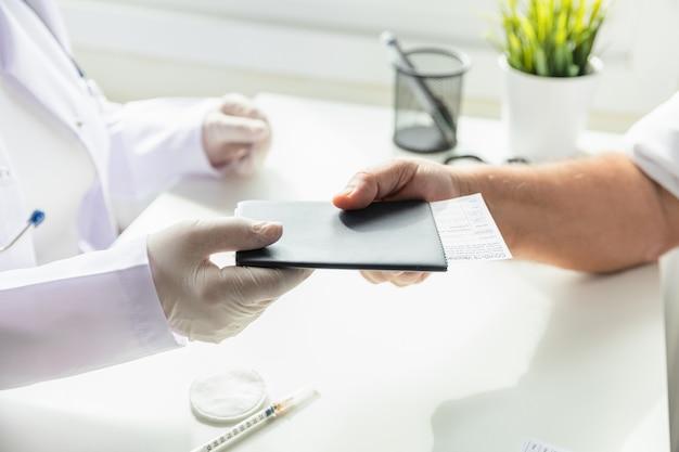 장갑을 낀 의사가 코로나 바이러스 예방 접종 카드, 코로나 19 예방 접종 카드와 함께 환자 여권을 해외 여행에 전달합니다. 선택적 초점.