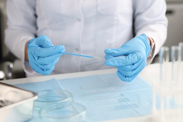 장갑을 낀 의사는 실험실에서 얼룩과 유리를 위한 브러시를 보유하고 있습니다. 세포배럴 비뇨생식기 개념