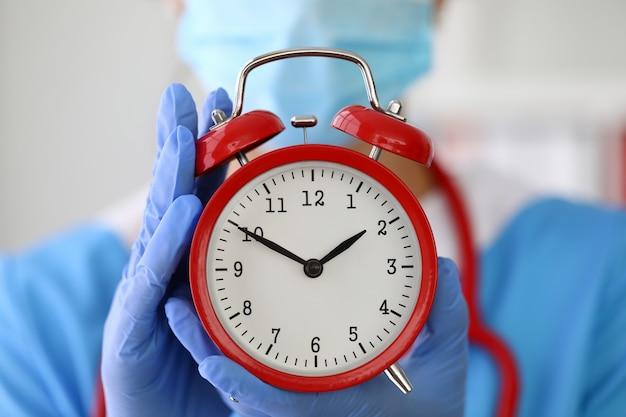 手袋をはめた医者は赤い目覚まし時計のクローズアップを保持します。