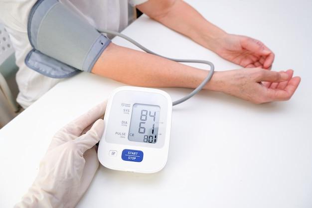 手袋をはめた医師は、白い背景の人の血圧を測定します。動脈性低血圧。手と眼圧計がクローズアップ。
