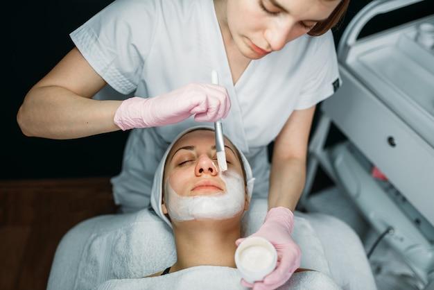 Доктор в перчатках натирает крем на лицо пациента