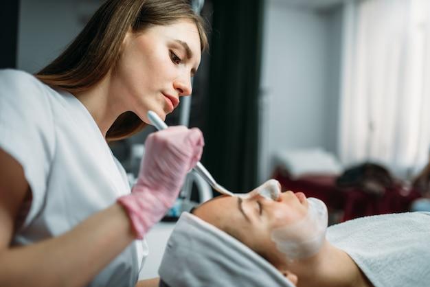 手袋をはめた医師が患者の顔にクリームをこすりつける
