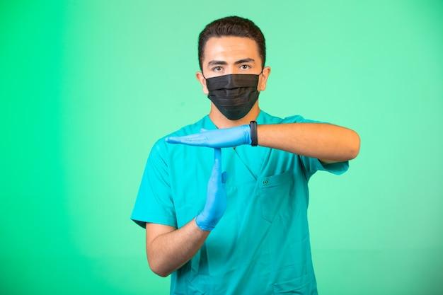 Доктор в зеленой форме и маске делает жесты руками.