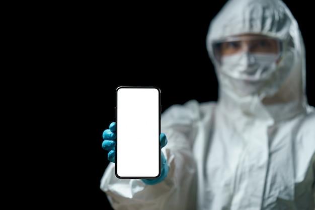 テキストの空白の白い画面を持つスマートフォンを保持している化学防護服(ppe)の医師。コロナウイルス、covid-19発生の概念。