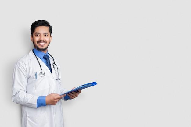 白い壁に隔離された、カメラを見て患者ファイルまたは医療記録を保持している白衣の医師