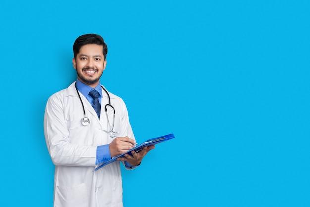 青い壁に隔離された、患者ファイルを保持している、またはカメラを見て医療記録を書いている白衣の医師