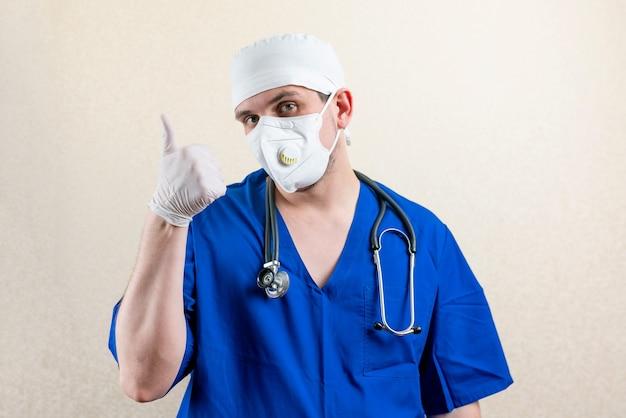 엄지손가락을 보여주는 마스크와 모자에 의사. 고품질 사진