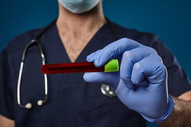 마스크를 쓴 의사, 파란색 일회용 장갑, 의료 스크럽, phonendoscope. 그의 손에 녹색 모자와 함께 빨간색 실험실 테스트 튜브를 들고. 파란색 배경입니다. 코로나바이러스 연구. 코로나 바이러스 감염증 -19 : 코로나 19. 클로즈업, 복사 공간
