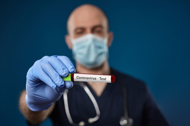 마스크 파란색 장갑 의료복을 입은 의사는 파란색 손에 녹색 모자가 있는 빨간색 실험실 테스트 튜브를 들고...