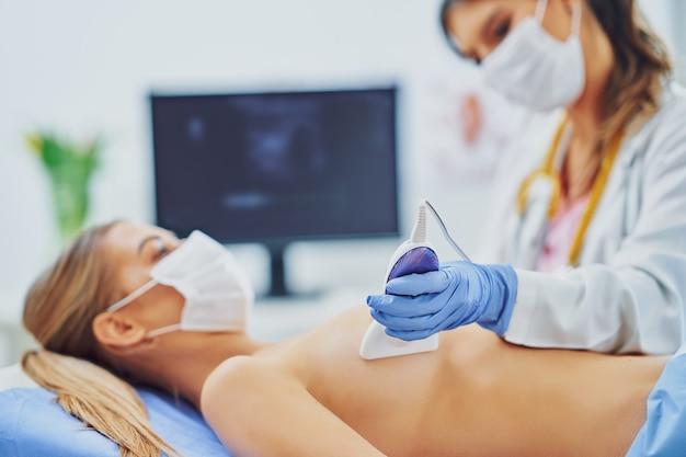 Доктор в маске проверяет грудь своей пациентке
