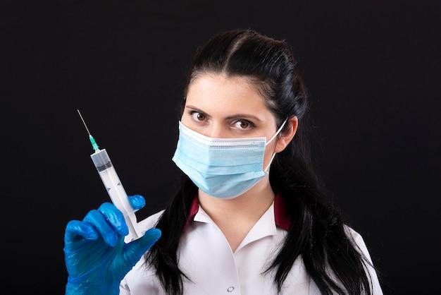 Доктор в маске, держащий шприц, крупным планом, концепцию вакцинации и иммунизации, изолированную на темноте Premium Фотографии