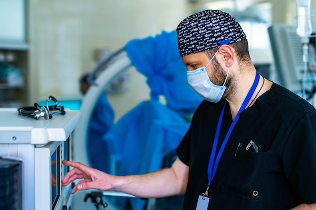Доктор в маске. профессиональный хирург. серьезный мужчина в медицинской форме, стоящий в операционной. работа в больнице