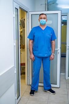 Доктор в маске. специальная современная палата в больнице. открылась дверь в операционную.
