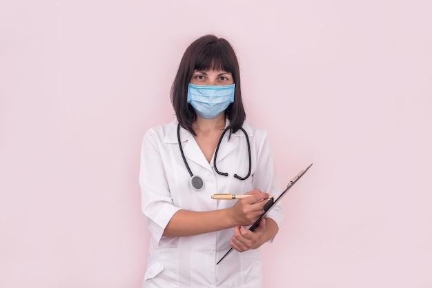 クリップボードに処方箋とマスクの医者