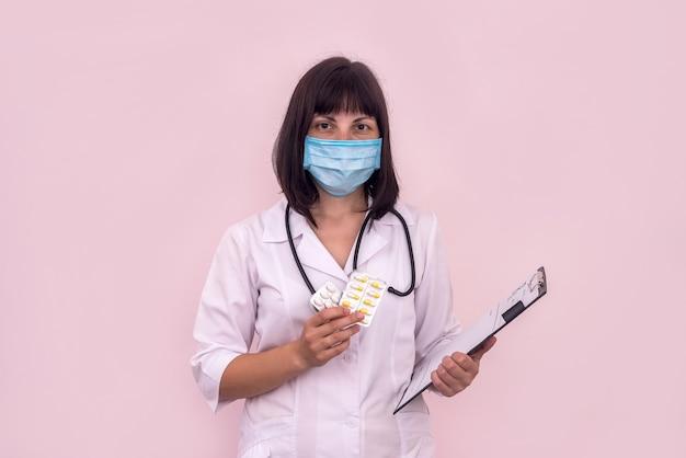 いくつかの錠剤を示す処方箋とマスクの医師