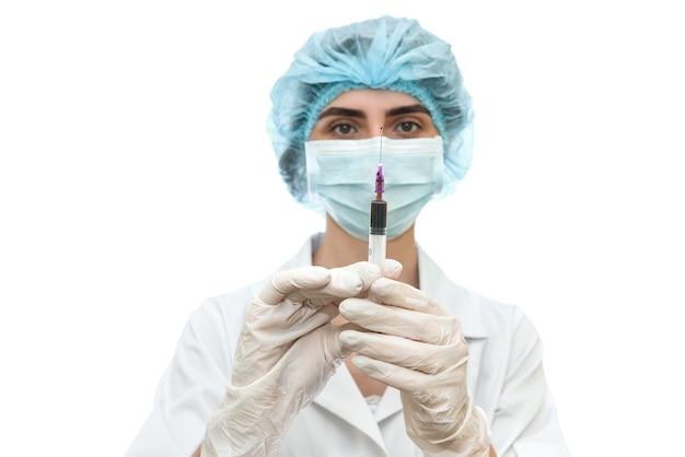 Доктор в маске со шприцем, изолированным на белом