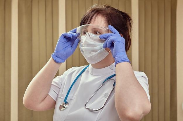 Врач в медицинской лицевой хирургической маске и защитных перчатках носит очки для защиты органов дыхания во время пандемии коронавирусной инфекции covid 19.