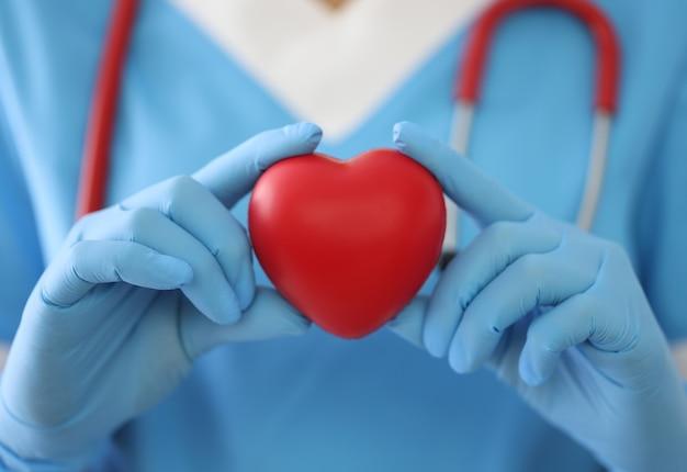 Доктор в медицинских перчатках держит игрушечное сердце крупным планом