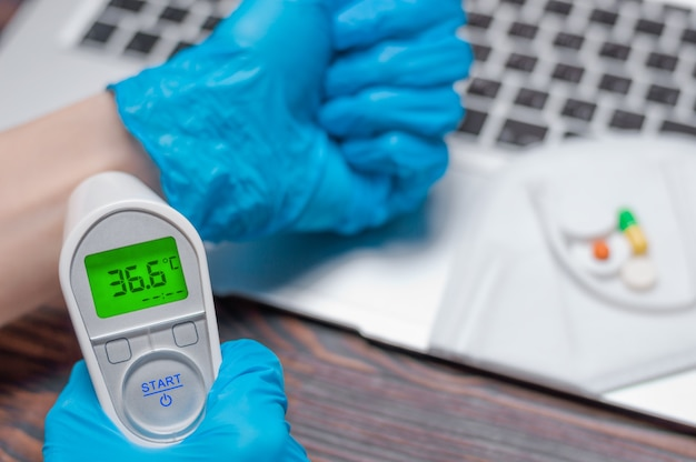 의료용 장갑을 쓴 의사는 적외선 온도계로 온도를 측정합니다.