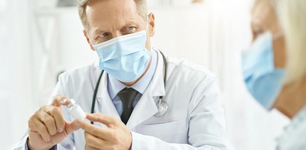 患者と投薬について話し合う医療用マスクの医師