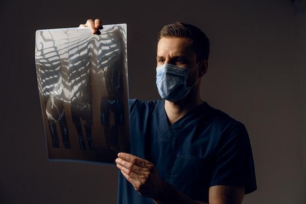 病気の患者のx線スキャンを保持しているコロナウイルスcovid-19の保護のための医療マスクの医師。コンピュータ断層撮影。
