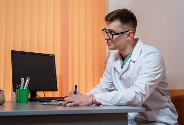 診療所の医師。デスクの医療専門家。スクラブとグラスに座っています。処方箋を書く。閉じる。