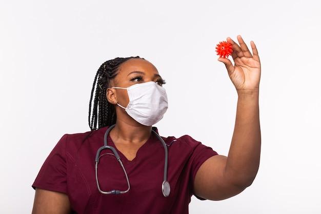 Врач в медицинской защитной маске держит модель коронавируса.