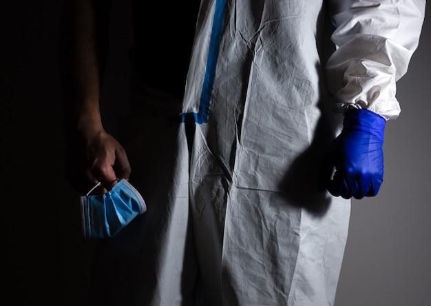 医療用防護服と手袋をはめた医師がマスクを手に持っている。ウイルスのパンデミックの終焉。ウイルスの流行による保護マー。コロナウイルス(covid-19)。ヘルスケアのコンセプト。