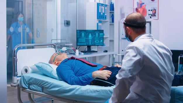 現代の私立病院または診療所の医師が、呼吸を良くするために酸素マスクを着用している患者と話している。コロナウイルスcovid-19ヘルスケア危機の世界的大流行。 rに対して呼吸するための助けを得る