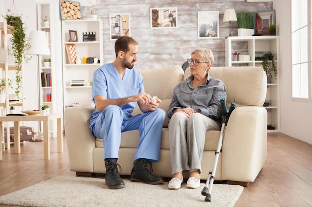 彼女の新しい丸薬について年配の女性と話しているナーシングホームの医者。