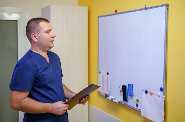 ボードの近くに立っているオフィスの医師。ノート付きホワイトボード。プロのスペシャリストのコンセプト。パンデミックとcovid-19に関する会議。
