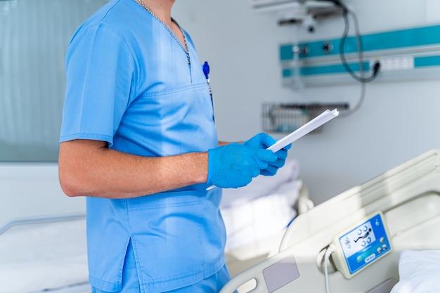 Врач в операционной с папкой в руках. врач в больничной палате. современное медицинское образование. выборочный фокус.