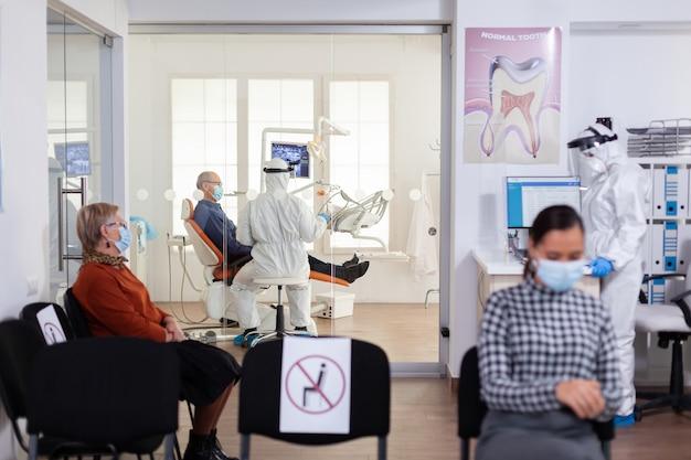 コロナウイルスによる世界的大流行の際に、バイザーを維持している口腔病学オフィスの上級患者に相談するおしっこスーツの医師