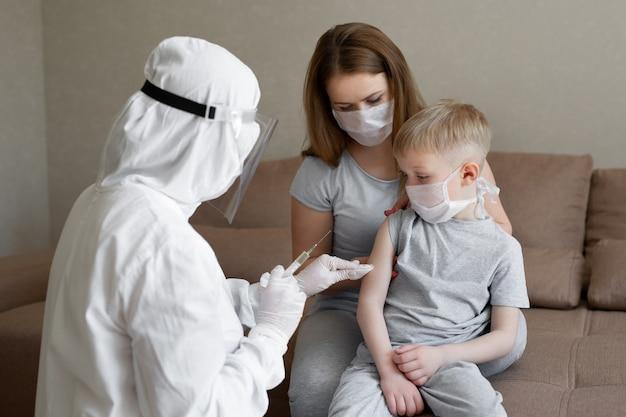 개인 보호 복을 입은 의사 또는 ppe 주사 백신 주사