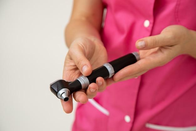 Врач в розовой медицинской одежде держит в руках отоскоп. медицинские исследования. профилактические осмотры. медицина и страхование. охрана здоровья. современные медицинские инструменты.