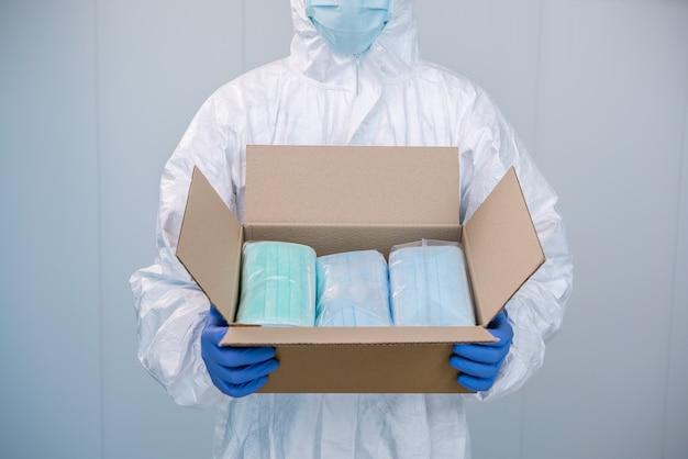 Врач в сиз и медицинской маске открывает коробку и показывает упаковку новых хирургических масок, которые он должен взять с собой во время пандемии covid19.