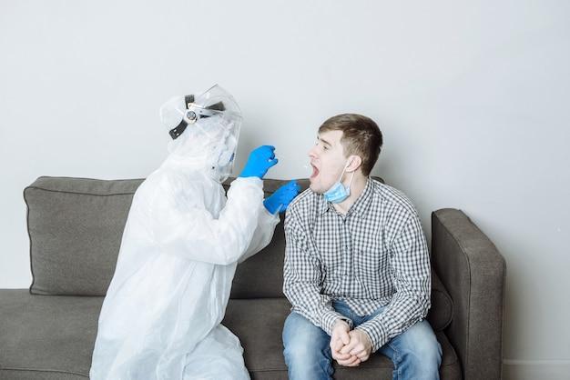 Врач в защитном костюме сиз берет мазок на образец вируса коонавируса covid-19 у пациента