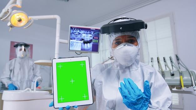 緑色の画面でタブレットを表示し、歯科x線撮影と歯の感染症の診断を説明するppeスーツの医師。モックアップ、コピースペース、クロマディスプレイを指すカバーオールの口腔病学スペシャリスト