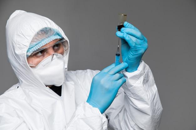 Доктор в защитной одежде держит вакцину коронавируса covid-19 и смотрит на нем, портрет крупным планом. защита от covid-19. концепция пандемии, эпидемии, вакцинации.