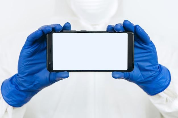 Врач в защитной одежде, респираторе, очках, перчатках держит телефон. врачам настоятельно рекомендуется оставаться дома во время эпидемии коронавируса. covid-19