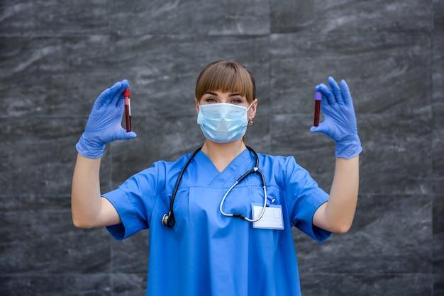 보호 장갑 및 추상적 인 배경에 빨간색 테스트 튜브를 들고 마스크 의사
