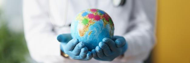 ウイルスのクローズアップで地球を保持している保護手袋の医師