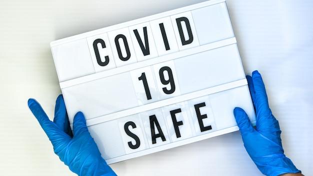 Covid 19 safe라는 텍스트가 있는 라이트박스를 들고 보호 장갑을 끼고 있는 의사. 학교로 돌아가다. 사회적 거리두기. 학교 검역 개념입니다. 공간을 복사합니다. 코로나 2차 유행