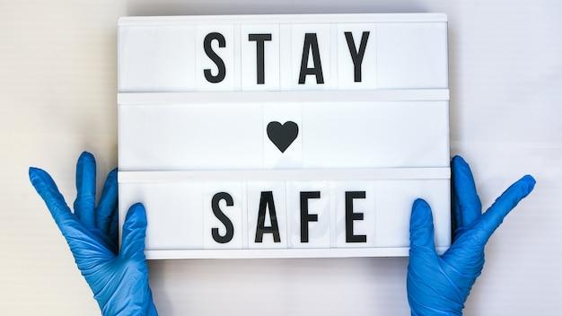 Stay safe라는 텍스트가 있는 라이트박스를 들고 있는 보호 장갑을 끼고 있는 의사. 학교로 돌아가다. 사회적 거리두기. 학교 검역 개념입니다. 공간을 복사합니다. 코로나 2차 유행