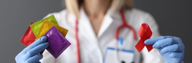 빨간 리본 및 콘돔 근접 촬영 에이즈 하루 개념을 들고 보호 장갑에 의사