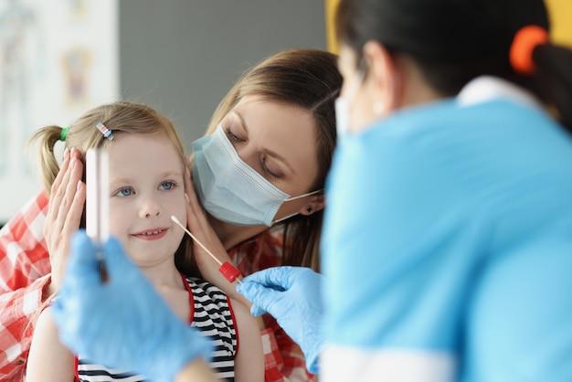 클리닉에서 어린 소녀에게 면봉으로 얼룩을 만드는 보호 마스크 의사